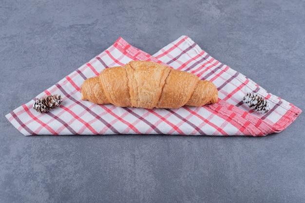 Croissant fraîchement sorti du four sur une serviette en coton rose.