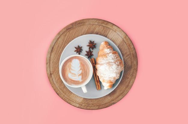 Croissant frais au four avec tasse de café et latte art, cannelle