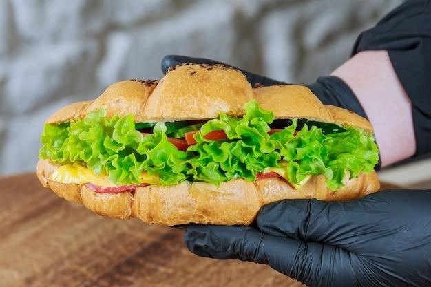 Croissant frais au jambon et salade dans la main d'un serveur dans un gant noir