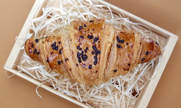 Un croissant frais et croustillant à grains entiers avec garniture au chocolat sur fond marron ou café avec espace de copie. dessert français traditionnel classique fraîchement sorti du four, pâtisseries. vue de dessus, mise à plat.
