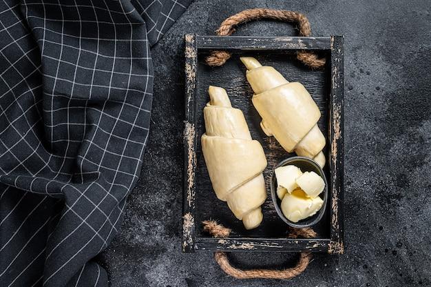 Croissant frais cru dans un plateau en bois. table noire. vue de dessus.