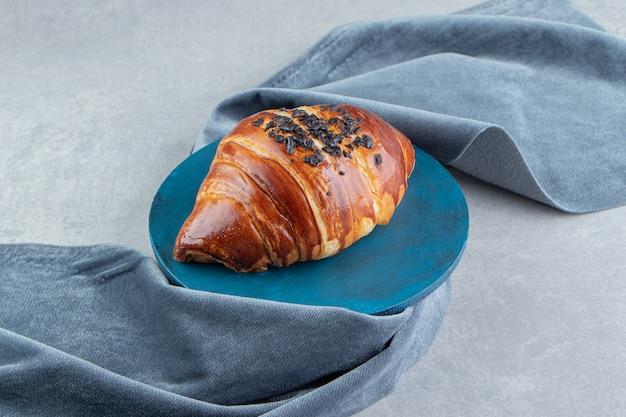 Croissant frais décoré de goutte de chocolat sur planche bleue.