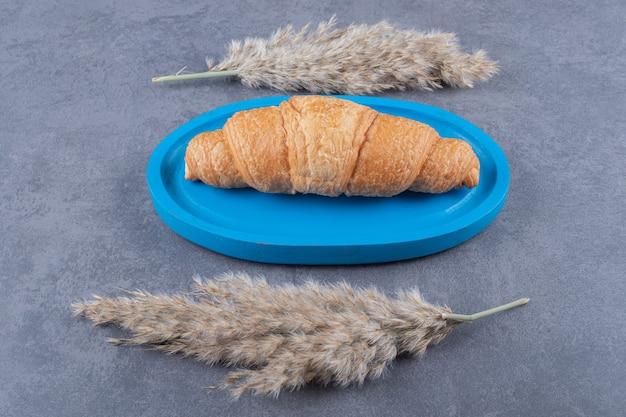 Croissant frais fait maison sur planche de bois bleue.