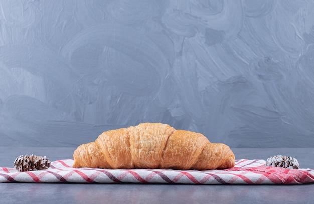 Croissant frais fait maison et pomme de pin sur fond gris.