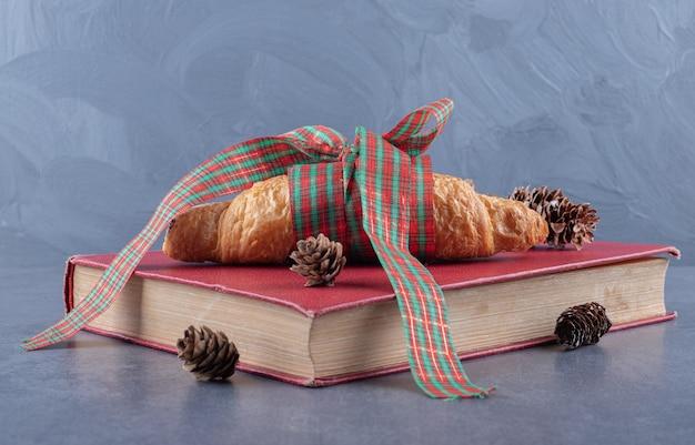 Croissant frais français classique sur livre rouge.