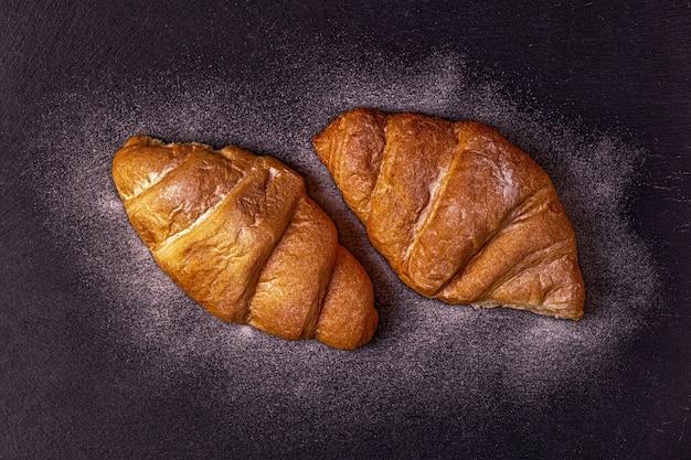 Croissant frais sur table sombre.