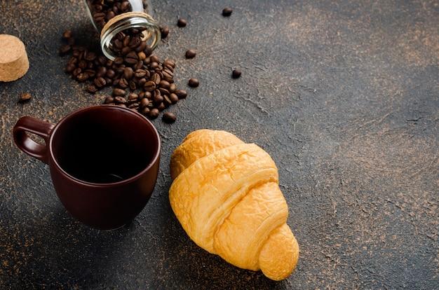 Croissant frais avec une tasse de café noir et grains de café sur fond de béton foncé. le concept de boissons chaudes, petit déjeuner revigorant.