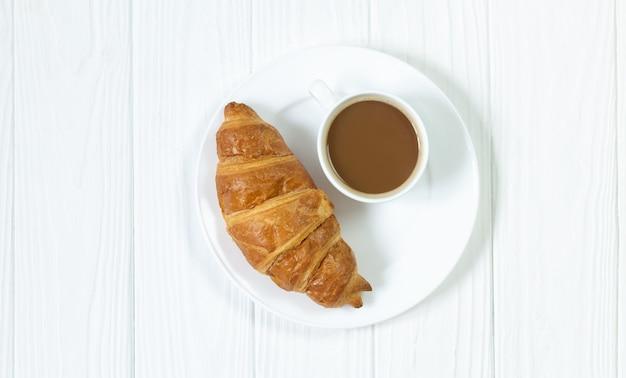 Croissant frais et tasse de café sur la vue de dessus de plaque blanche
