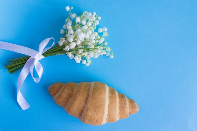 Croissant français sur bleu avec le muguet. petit déjeuner