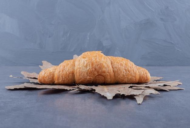 Croissant français fraîchement sorti du four sur fond gris.