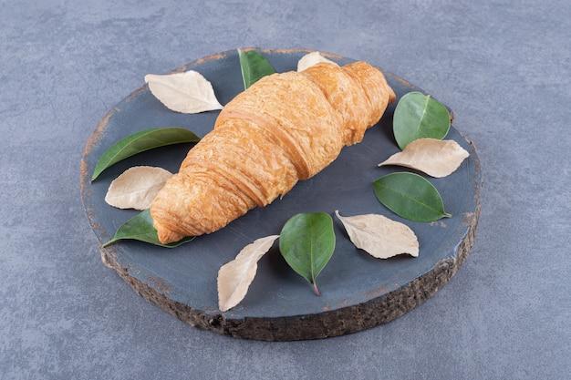 Croissant français fraîchement sorti du four sur planche de bois gris sur fond gris.