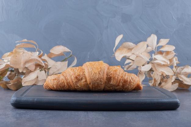 Croissant français fraîchement sorti du four sur planche de bois gris.