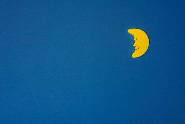 Croissant jaune lune contre le ciel bleu nuit. papier d'application à droite.