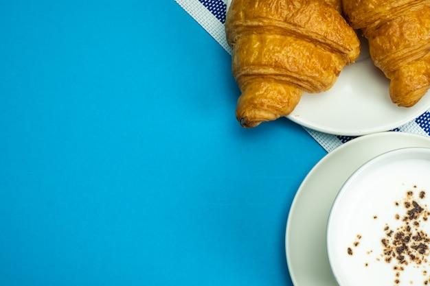 Croissant et lait chaud sur bleu