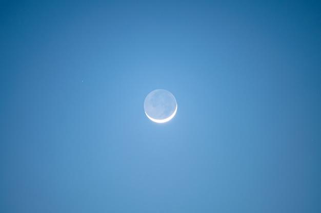 Croissant de lune brillant dans le ciel bleu