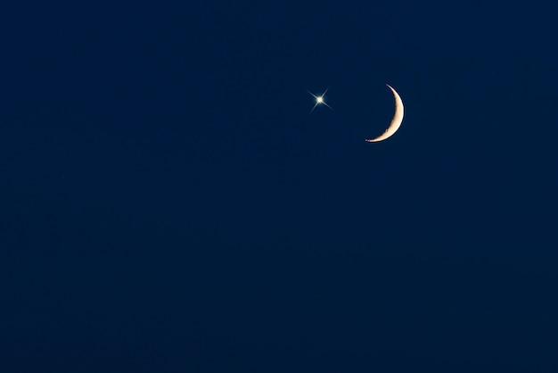 Croissant de lune avec étoile sur ciel bleu foncé, photo pour fond de ramadan ou ramazan