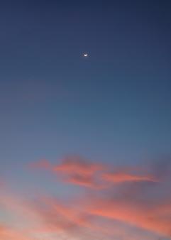 Le croissant de lune sur des nuages colorés dans le ciel bleu au crépuscule
