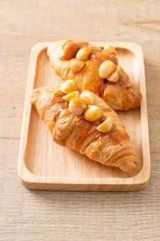 Croissant avec macadamia et caramel sur plaque de bois