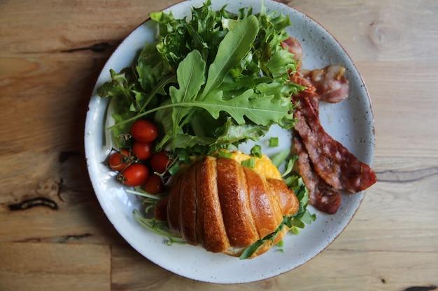 Croissant avec oeuf et bacon sur fond de bois