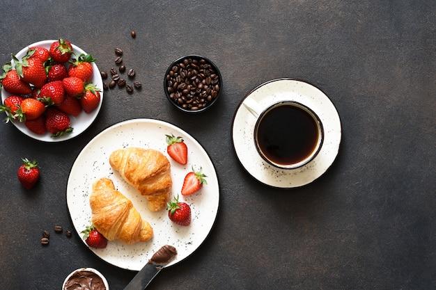 Croissant à la pâte de chocolat et une tasse de café, fraises sur la table de la cuisine. • collation traditionnelle ou petit déjeuner.