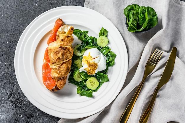 Croissant sandwich au saumon salé servi avec salade fraîche de feuilles d'épinards, œuf et légumes