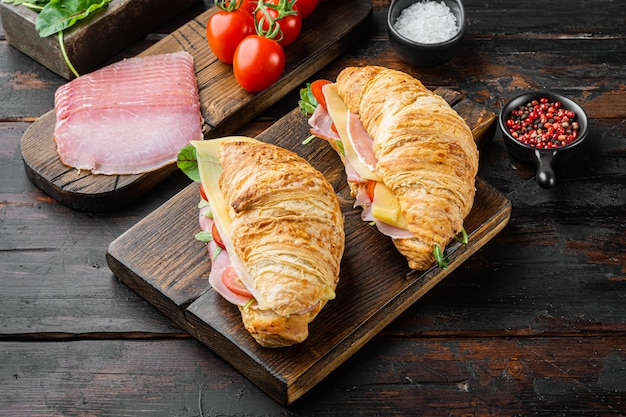 Croissant ou sandwich frais avec salade, jambon, jambon, ensemble de prosciutto, avec herbes et ingrédients, sur une vieille table en bois foncé