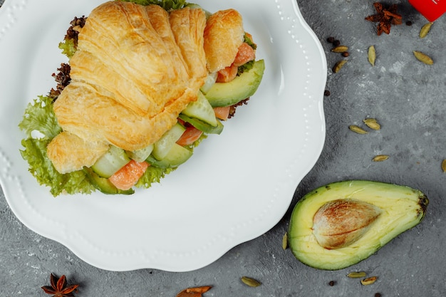 Croissant sandwich avec poisson rouge, avocat, légumes frais et roquette sur planche de schiste noir sur fond de pierre noire. concept de nourriture saine.