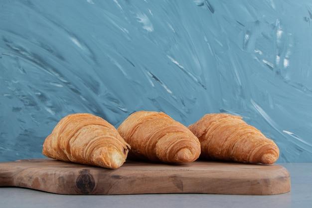 Croissant savoureux à bord, sur le fond de marbre. photo de haute qualité