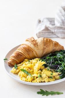 Croissant servi avec œufs brouillés et épinards sur assiette. petit-déjeuner.