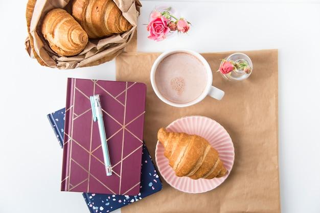 Croissant et une tasse de cacao sur un bureau blanc à côté de blocs-notes. concept de pause. vue de dessus, plat poser