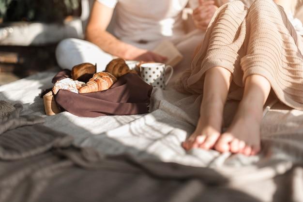 Croissant et tasse à café près du couple assis sur le lit