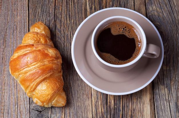 Croissant avec tasse de café sur une table en bois
