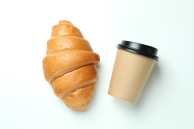 Croissant et tasse de papier sur blanc