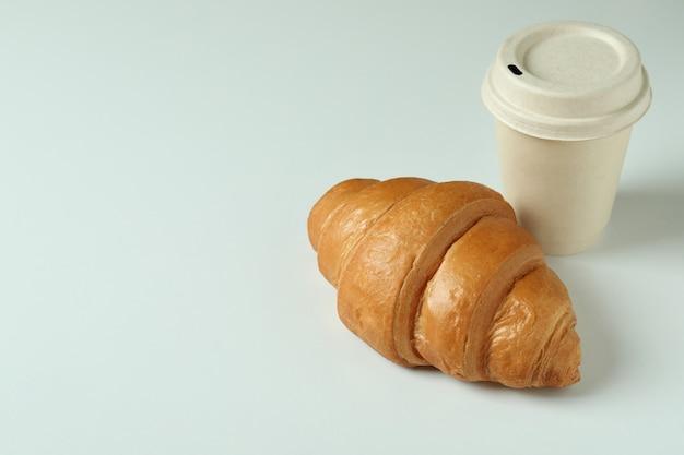 Croissant et tasse en papier sur gris clair