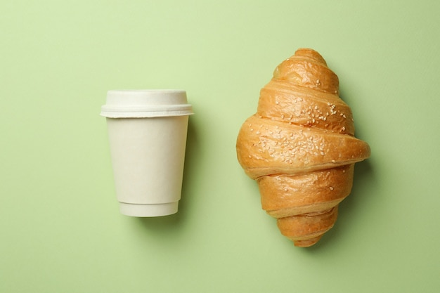 Croissant et tasse de papier sur vert