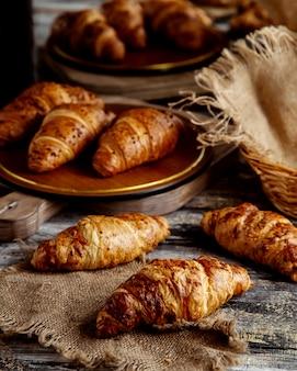 Croissants au beurre placés sur des étoffes en lin et des paniers en paille