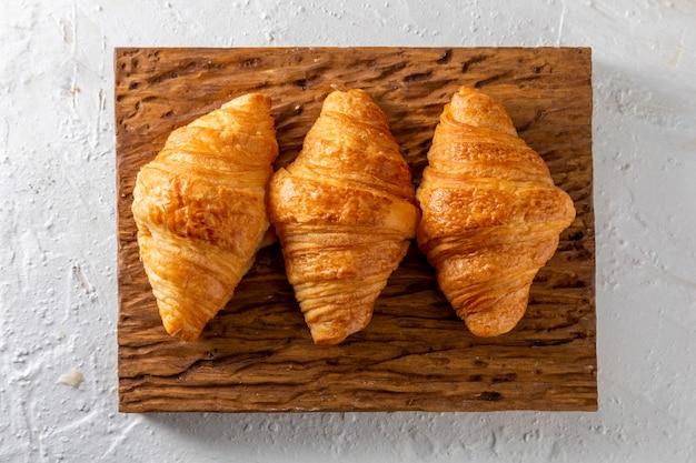 Croissants au beurre sur une planche de bois rustique.