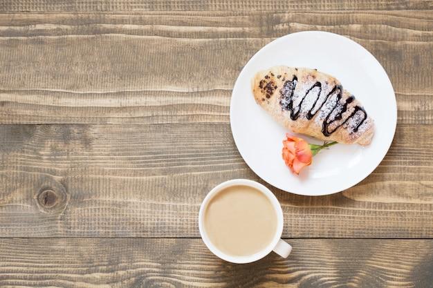 Des croissants au chocolat fraîchement sortis du four et une tasse de café sur une planche de bois. vue de dessus. concept de petit-déjeuner féminin. espace de copie.
