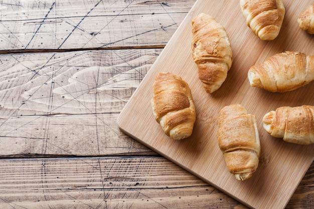 Croissants au chocolat remplissant sur fond en bois.