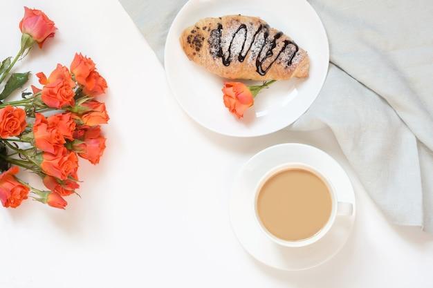 Des croissants au chocolat et une tasse de café sur une table blanche. vue de dessus. petit déjeuner féminin. espace de copie.