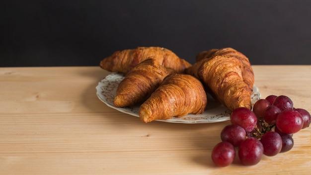 Croissants au four sur une plaque en céramique et raisins mûrs sur une table en bois