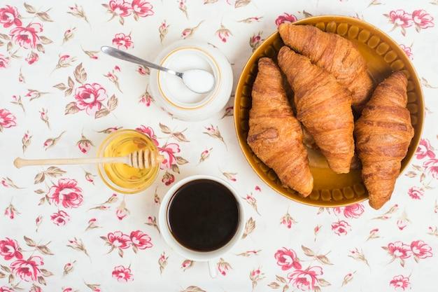Croissants au four; thé; miel et lait en poudre sur fond floral