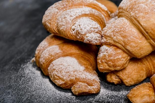 Croissants au sucre en poudre sur table grise.