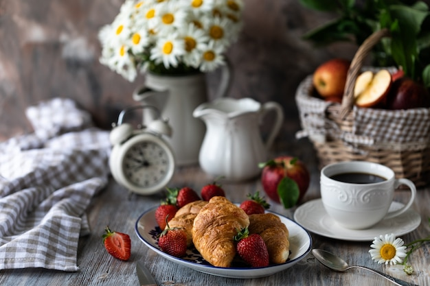 Croissants aux fraises rouges fraîches avec une tasse de café sur une table en bois et bouquet de marguerites dans une cruche.