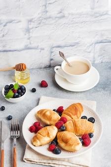 Croissants aux framboises fraîches et myrtilles sur un béton foncé. copiez l'espace. concept de petit déjeuner café miel.