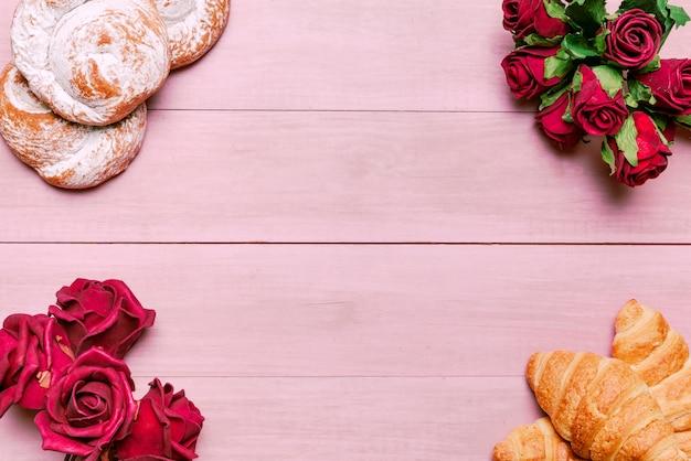 Croissants avec bouquet de roses rouges et petits pains
