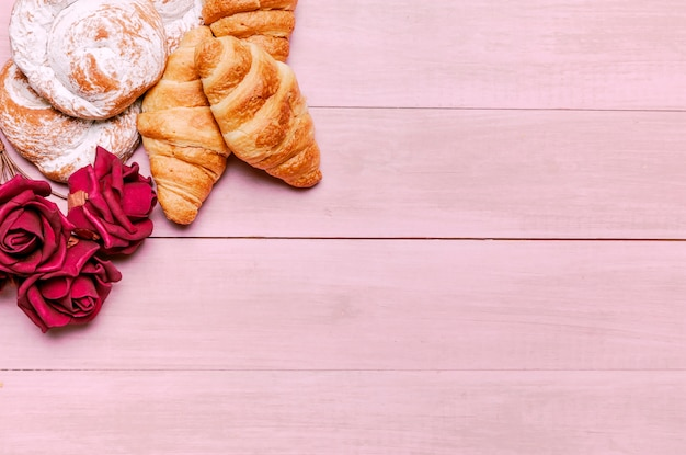 Croissants avec des bourgeons de roses rouges et des petits pains