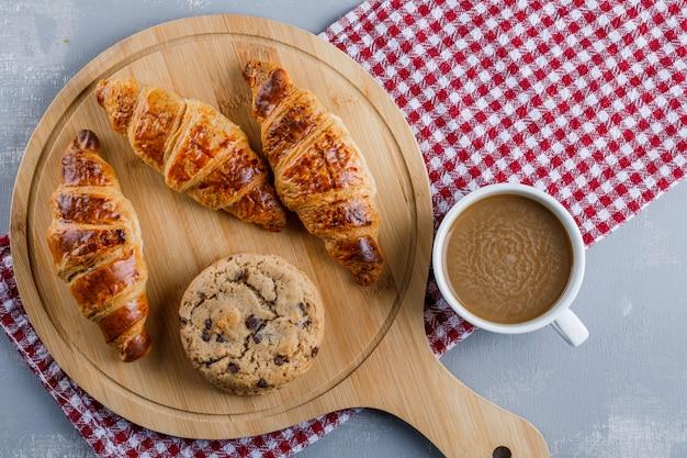 Croissants avec café, biscuits, planche à découper à plat sur du plâtre et un chiffon de pique-nique