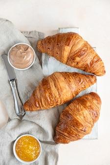 Croissants à la confiture et crème au chocolat, fond béton clair. mise au point sélective. vue de dessus.