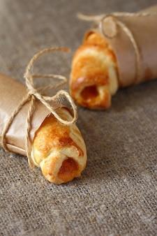 Croissants à la confiture de pêche enveloppés dans du papier kraft et attachés avec des cordes avec des arcs sur une nappe grise rugueuse.